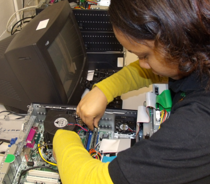 A Student Volunteer Troubleshooting and Repairing Computers